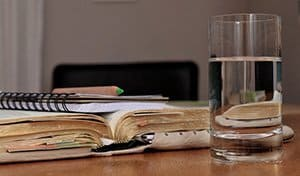 glass of water next to some books