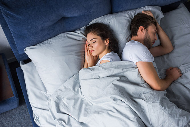 photo of a couple sleeping back to back in bed