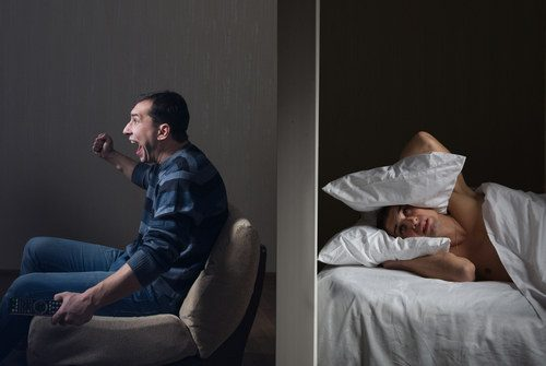 photo of a man trying to sleep in one room with a noisy neighbor in the room next to him