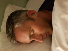 photo of ethan green wearing earplugs in bed