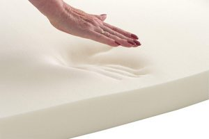 woman touching a memory foam mattress topper
