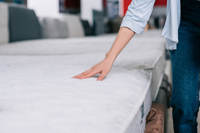 photo of a woman testing a mattress topper in a shop