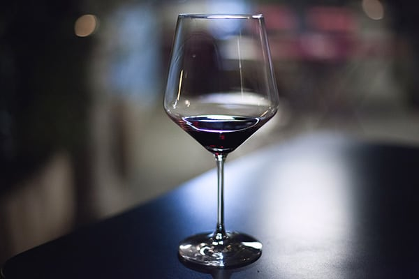 a glass of wine on a table at night