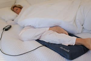 image of the relaxis vibration pad being used by a woman