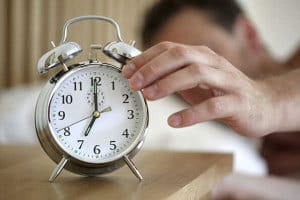 man sleeping and pressing the alarm clock