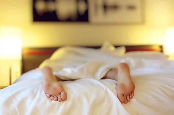 image of a person sleeping in bed with their feet hanging out
