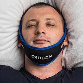 image of a man sleeping with an anti-snoring chin strap