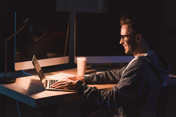 photo of a man working late at night on his laptop