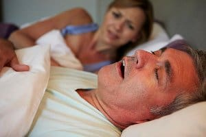 image of a man snoring and keeping his partner awake in bed