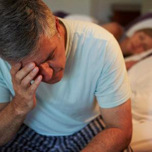 older man awake in his bed
