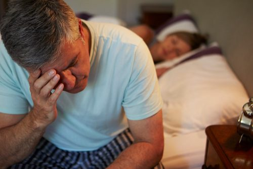 photo of an older man sitting on his bed awake in the night