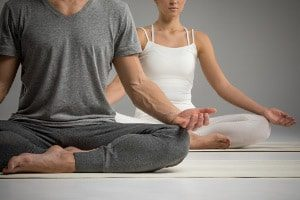 photo of a man and woman doing a form of yoga meditation
