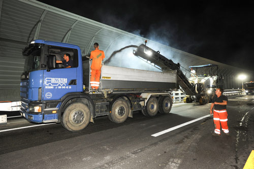 photo of night construction workers on a road