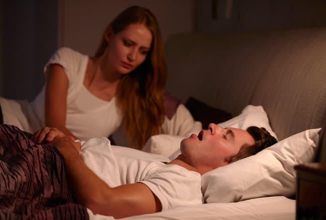 woman awake in bed next to man snoring