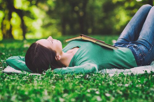 photo of a woman relaxing outside in a park with a book