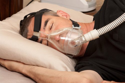 man with apnea wearing a cpap machine