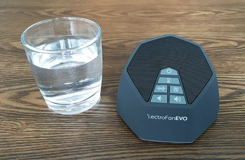 lectrofan evo white noise machine next to a small glass of water showing it is a compact size