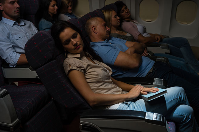 photo of different people sleeping in an airplane cabin