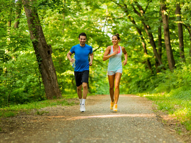 photo of a man and woman running in a forrest