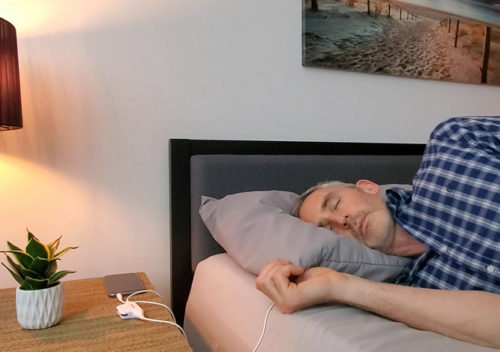 photo of ethan green lying down using the pillow speaker