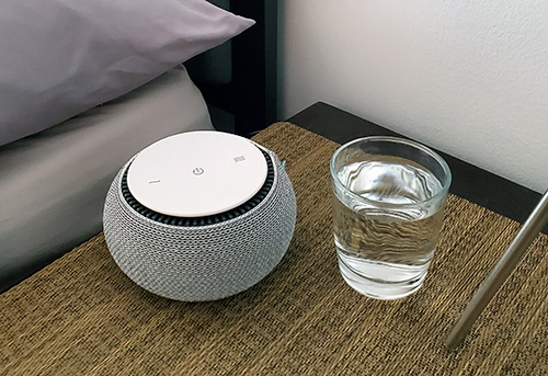 photo showing the SNOOZ on a nightstand next to a glass of water to compare the size