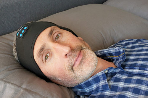 photo of the author, ethan green, wearing the lavince headphones in bed