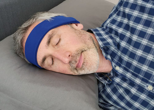 the author ethan green wearing the sleepphones while lying on his side