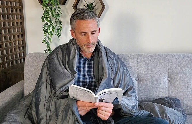 the article author ethan green using the luxome weighted blanket on the sofa