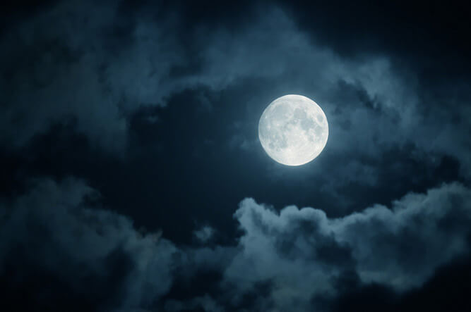 photo of a full moon at night with clouds