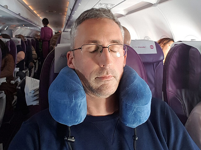 photo of ethan green using a travel pillow on a plane