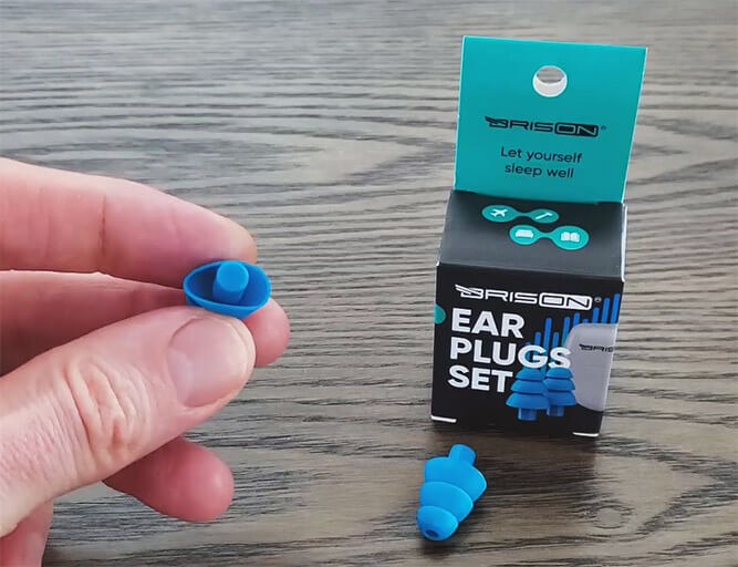 photo of the brison soft plastic/liquid silicone earplugs, and a hand demonstrating the small tip that's difficult to remove