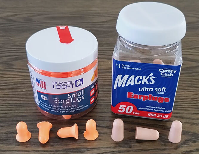 photo of the howard leight small and macks ultra soft earplugs, showing a sample of the earplugs on a table with the pots they come in