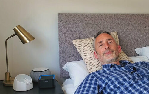 photo of ethan green in a bedroom with three white noise machines on the bedside table